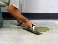 Repairing the cored holes in the concrete slab floor with fresh concrete and cleaning up the Summerside home.