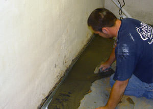 Restoring a concrete slab floor with fresh concrete after jackhammering it and installing a drain system in Grand-barachois.